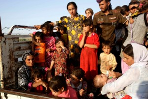 Displaced people from the minority Yazidi sect, fleeing the violence in the Iraqi town of Sinjar, re-enter Iraq from Syria at the Iraqi-Syrian border crossing in Fishkhabour