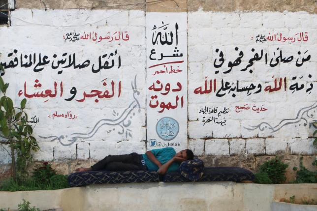 A man rests in front of a wall decorated with religious phrases written by members of al Qaeda's Nusra Front in Aleppo's Qadi Askar's neighborhood, Syria