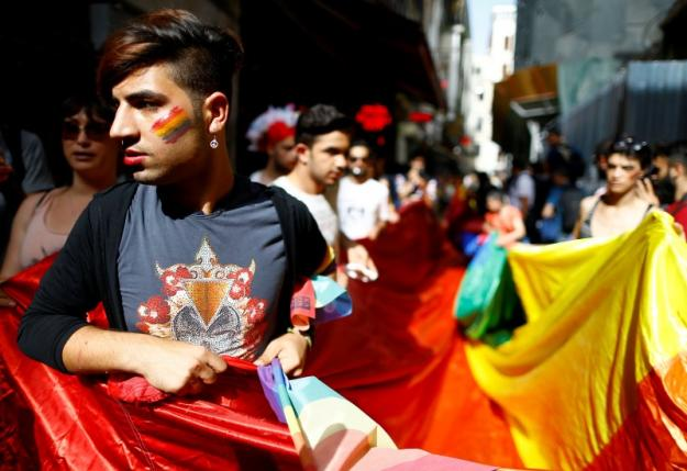 LGBT rights activists hold a rainbow flag during a transgender pride parade, which was banned by the governorship, in central Istanbul