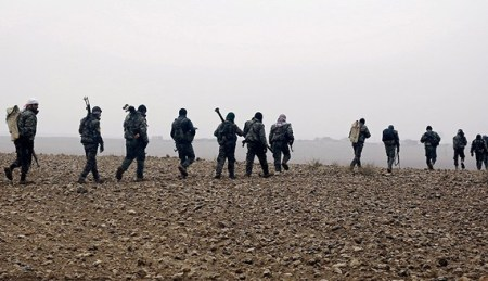 CORRECTION - Fighters from the Kurdish-Arab alliance known as the Syrian Democratic Forces walk near the village of Khirbet al-Jahshe, some 35 kilometres from al-Tabaqah on the western outskirts of Raqa as they advance towards the Islamic State (IS) group bastion on December 13, 2016.  / AFP / DELIL SOULEIMAN / The erroneous mention[s] appearing in the metadata of this photo by DELIL SOULEIMAN has been modified in AFP systems in the following manner: on December 13, 2016 instead of on December 14, 2016. Please immediately remove the erroneous mention from all your online services and delete it  from your servers. If you have been authorized by AFP to distribute it  to third parties, please ensure that the same actions are carried out by them. Failure to promptly comply with these instructions will entail liability on your part for any continued or post notification usage. Therefore we thank you very much for all your attention and prompt action. We are sorry for the inconvenience this notification may cause and remain at your disposal for any further information you may require.        (Photo credit should read DELIL SOULEIMAN/AFP/Getty Images)