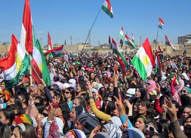 Syrian Kurds wave the Kurdish flag as th
