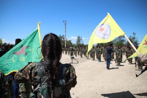Miliciana sostiene una bandera de las YPJ en el monte de Qereçox, durante la ceremonia en recuerdo de los miembros de las YPG/YPJ que fueron asesinados por el bombardeo turco un año atras. Abril 2018.