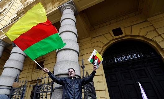 Supporters of Kurdish Democratic Union Party (PYD) former leader Saleh Muslim shout slogans in front of a Czech court, which released Muslim from custody, in Prague